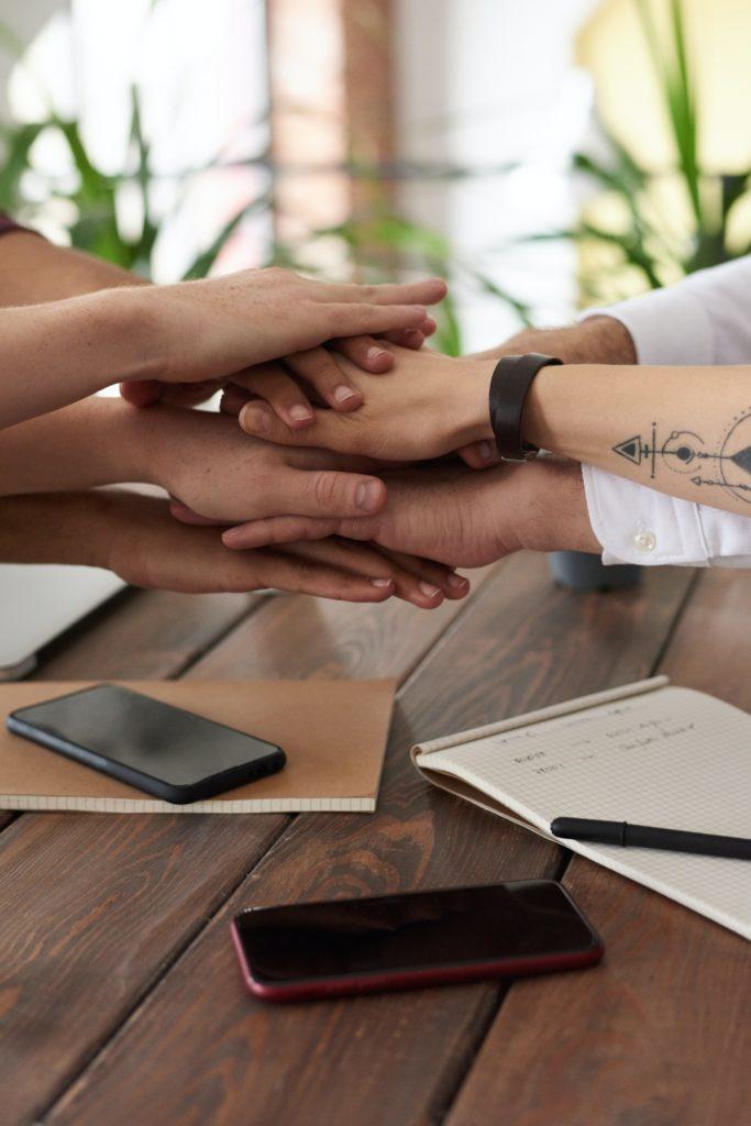 Idées reçues freelance sur la tarification et l'environnement social traduit par une photographie de main les unes sur les autres